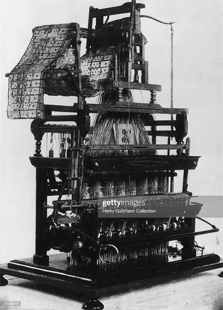 A jacquard weaving loom with punched cards used to control the design