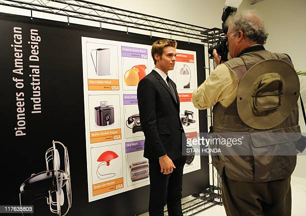 Jacque Loewy grandson of French industrial designer Raymond Loewy has his photograph taken by a large display of commemorative postage stamps...