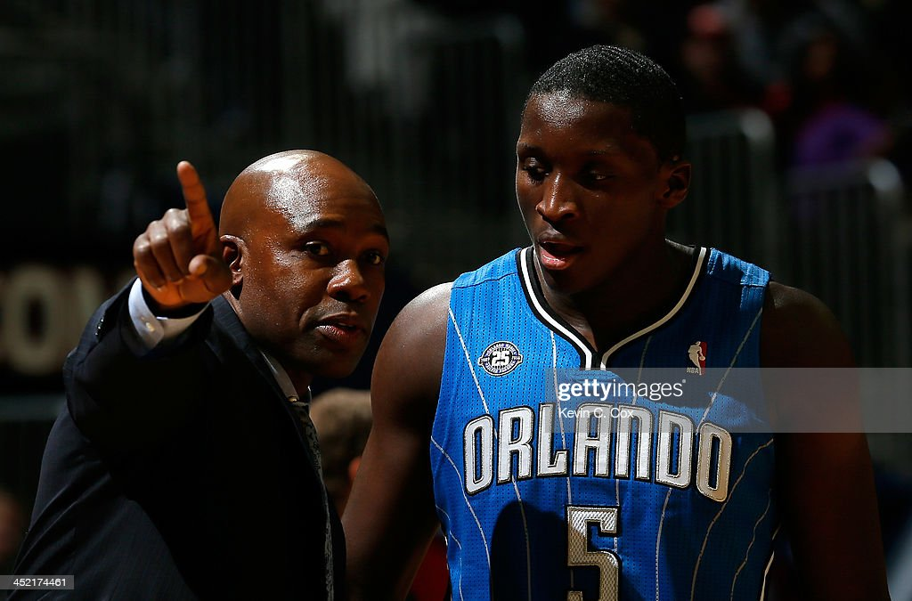 Jacque Vaughn of the Orlando Magic converses with Victor Oladipo #5 against the Atlanta Hawks at Philips Arena on November 26, 2013 in Atlanta, Georgia.