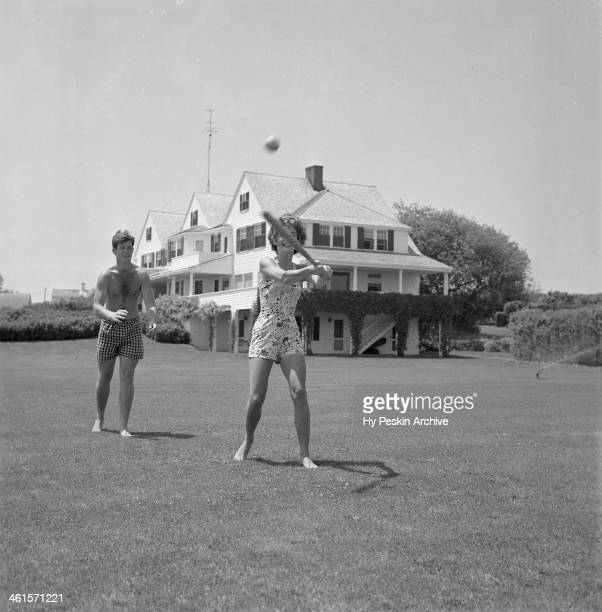Jacqueline Bouvier plays baseball with Edward Kennedy while on vacation at the Kennedy compound in June 1953 in Hyannis Port Massachusetts