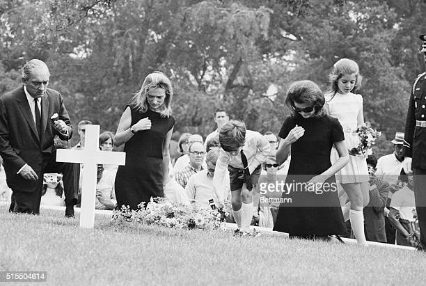 Jacqueline Kennedy and her children Caroline and John Jr kneel in prayer at the grave of the late President Kennedy after attending burial rites for...