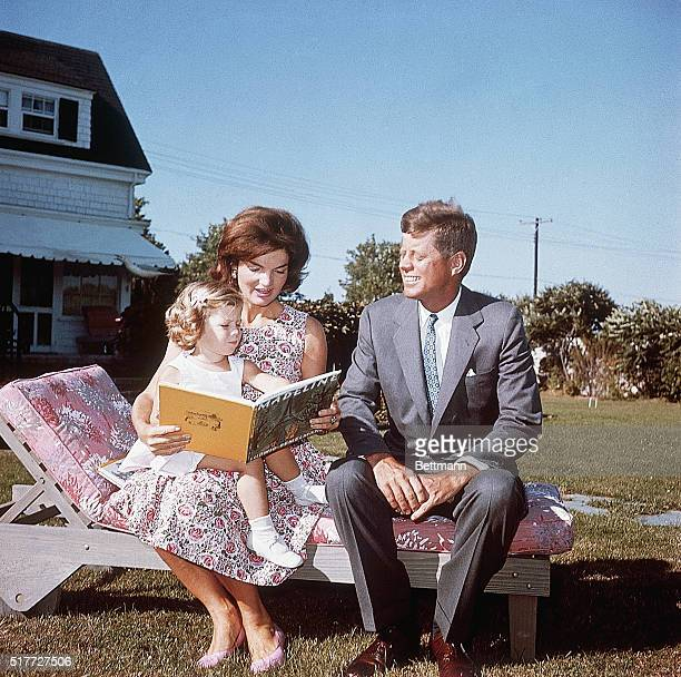 Jacqueline Kennedy and her husband Senator John F Kennedy sit on a lounge chair at their summer home Jacqueline reads to her daughter Caroline from a...