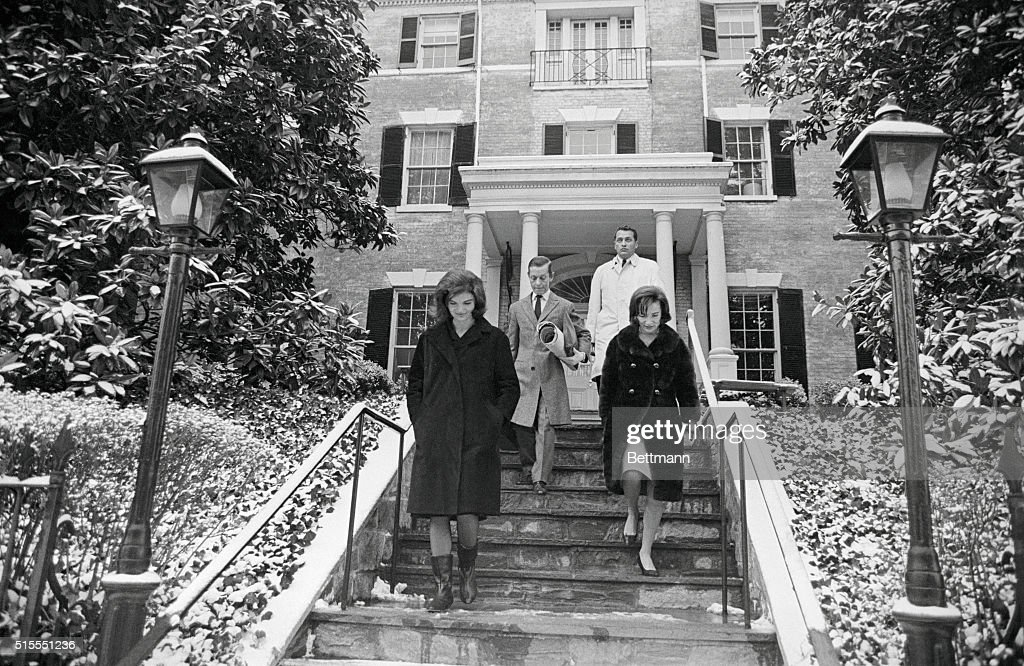 Jacqueline Kennedy and her sister Lee Radziwill are shown leaving the new Georgetown home, here 12/18, which Mrs. Kennedy recently purchased. The former First Lady inspected the home just prior to departing, with her two children, for Palm Beach, Florida, where they will spend the Christmas holidays. Man in center is William Baldwin a New York City interior decorator.