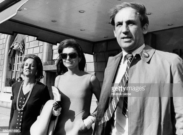 Jacqueline Kennedy Onassis center Katharine Graham president of the Washington Post and an unidentified man stand outside the Sheraton Plaza Hotel in...