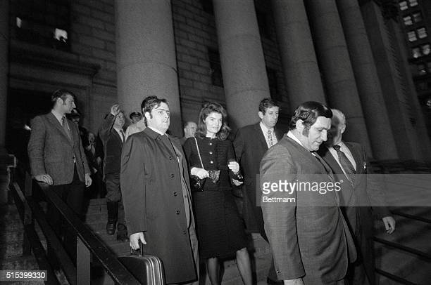 Jacqueline Kennedy Onassis is escorted from the US Attorney's office here by unidentified officials The former First Lady was questioned in the...