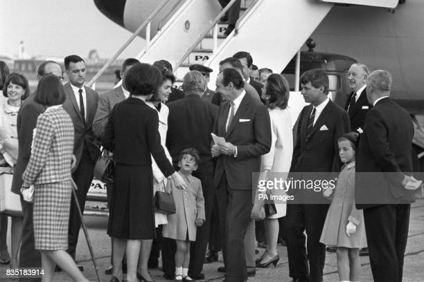 Jacqueline Kennedy surrounded by members of the family on arrival at London Airport by US Presidential Boeing 707 She is holding the hand of her son...