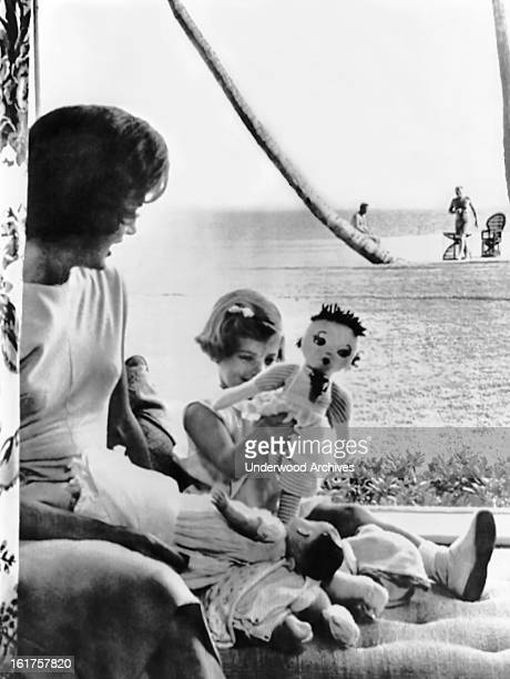Jacqueline Kennedy watches her daughter Caroline play with her dolls in the living room of the home in Palm Beach during their last preWhite House...
