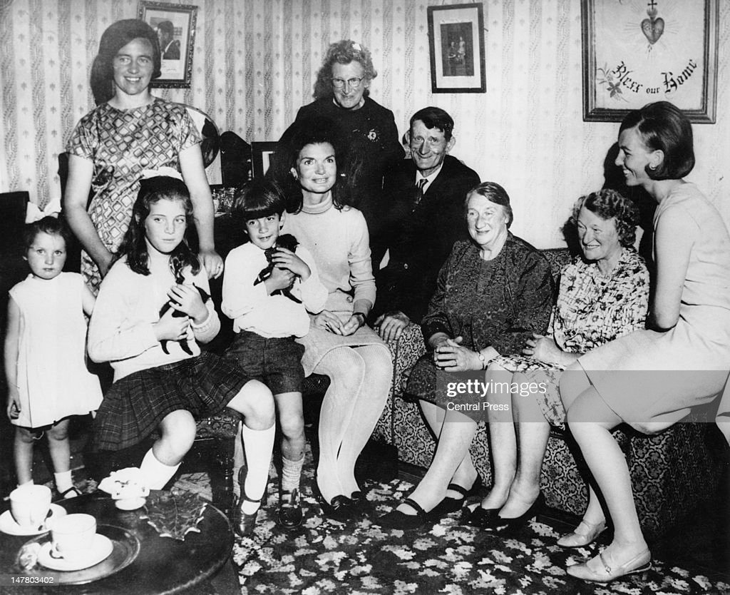 Jacqueline Kennedy (1929 - 1994) with her children Caroline and John in the living room of the Kennedy ancestral home at Dunganstown, County Wexford, during a family holiday in Ireland, 29th June 1967. In the family group is Mary Ryan, the late President's cousin, along with relations Maeve Rowe, Josie Grennan (Mrs Ryan's granddaughter), Mrs John Fenlon, James Kennedy (Mrs Ryan's brother), Margaret Kirwan (Mrs Ryan's sister), and Miss Mary Ryan (Mrs Ryan's daughter).
