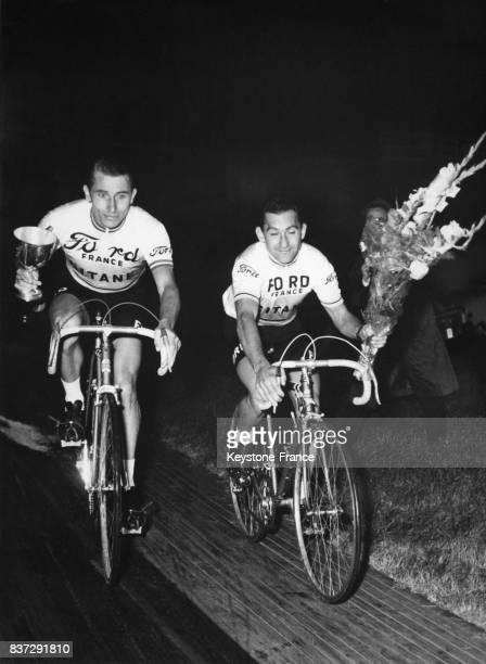 Jacques Anquetil et Jean Stablinski effectuant leur tour d'honneur après avoir remporté le Trophée Baracchi à Milan Italie le 6 novembre 1965