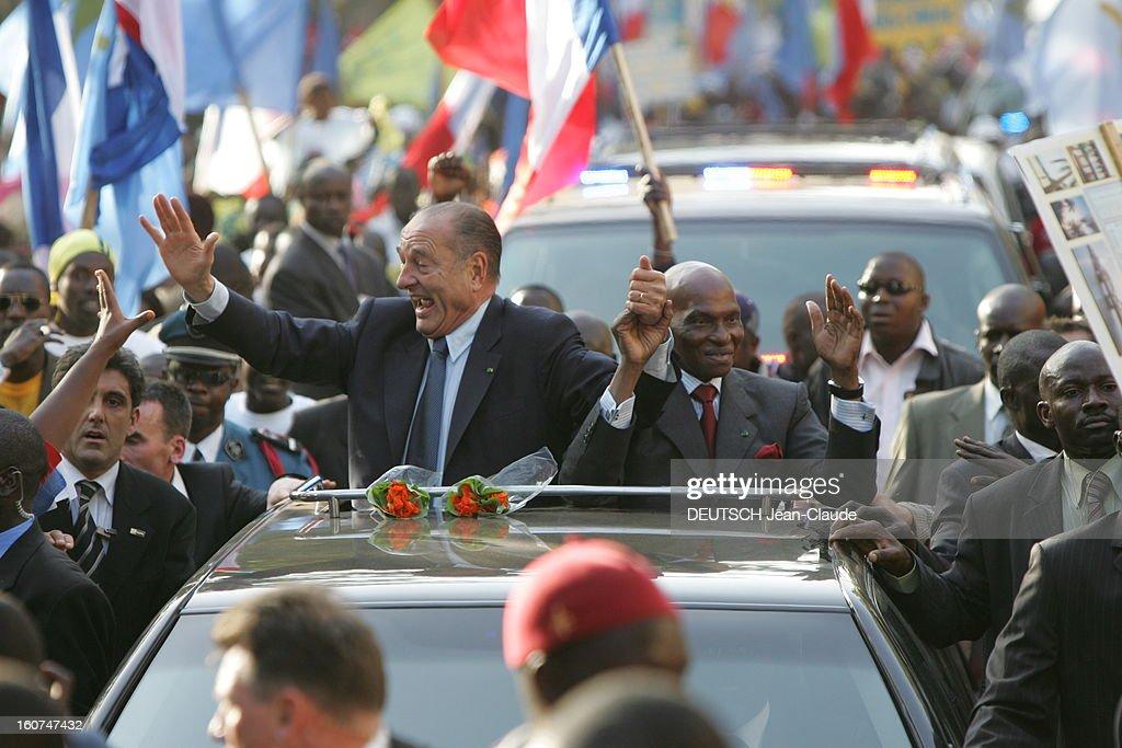 <a gi-track='captionPersonalityLinkClicked' href=/galleries/search?phrase=Jacques+Chirac&family=editorial&specificpeople=165237 ng-click='$event.stopPropagation()'>Jacques Chirac</a> Official Travel In Black Africa: Senegal. Accueil enthousiaste pour Jacques CHIRAC saluant la foule aux côtés du président sénégalais Abdoulaye WADE, debout à l'arrière d'une voiture, se tenant la main dans les rues de DAKAR..