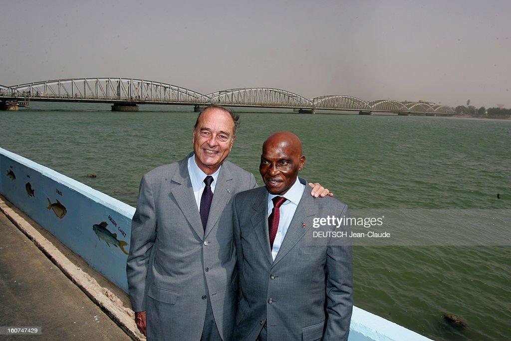 <a gi-track='captionPersonalityLinkClicked' href=/galleries/search?phrase=Jacques+Chirac&family=editorial&specificpeople=165237 ng-click='$event.stopPropagation()'>Jacques Chirac</a> Official Travel In Black Africa: Senegal. Plan de face souriant de Jacques CHIRAC posant le président sénégalais Abdoulaye WADE à SAINT-LOUIS au bord de l'eau, avec le pont Faidherbe en arrière plan.