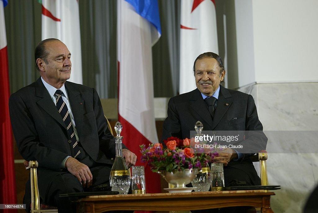 Jacques Chirac Visit In Algeria. Jacques CHIRAC et son homologue algérien Abdelaziz BOUTEFLIKA posant assis devant des drapeaux à ALGER.