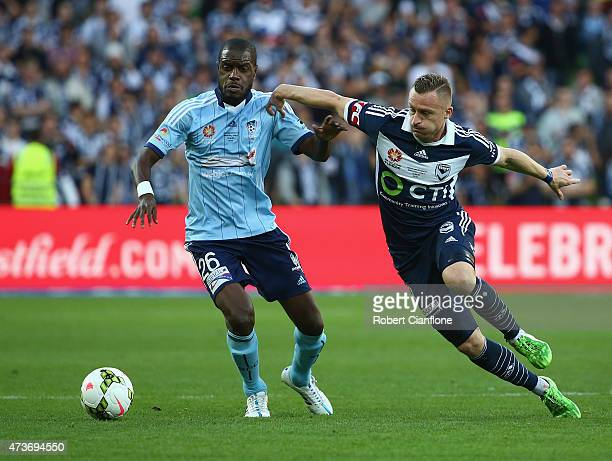 Jacques Faty of Sydney FC is challenged by Besart Berisha of the Victory during the 2015 ALeague Grand Final match between the Melbourne Victory and...