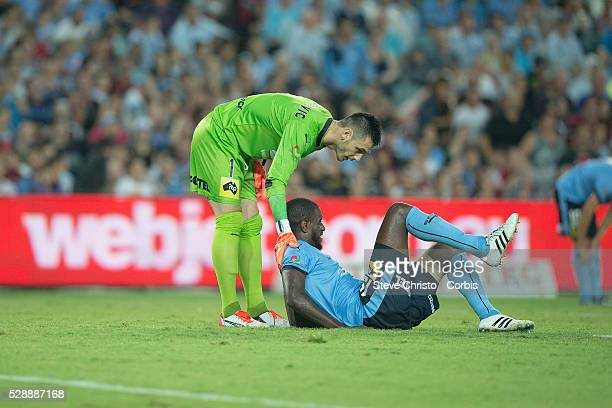 Jacques Faty of Sydney FC lies in pain and helped by teammate Vedran Janjetovic during the round 20 ALeague match between Sydney FC and Western...
