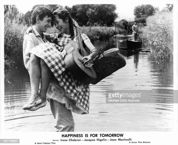 Jacques Higelin carrying Irene Chabrier over the water in a scene from the film 'Happiness Is For Tomorrow' 1961