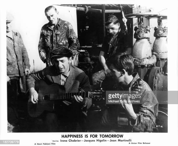 Jacques Higelin playing guitar with fellow guitarist in a scene from the film 'Happiness Is For Tomorrow' 1961