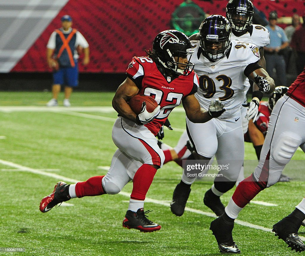 Jacquizz Rodgers of the Atlanta Falcons carries the ball against DeAngelo Tyson of the Baltimore Ravens at the Georgia Dome on August 9 2012 in...