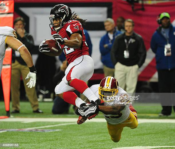 Jacquizz Rodgers of the Atlanta Falcons carries the ball against DeAngelo Hall of the Washington Redskins at the Georgia Dome on December 15 2013 in...