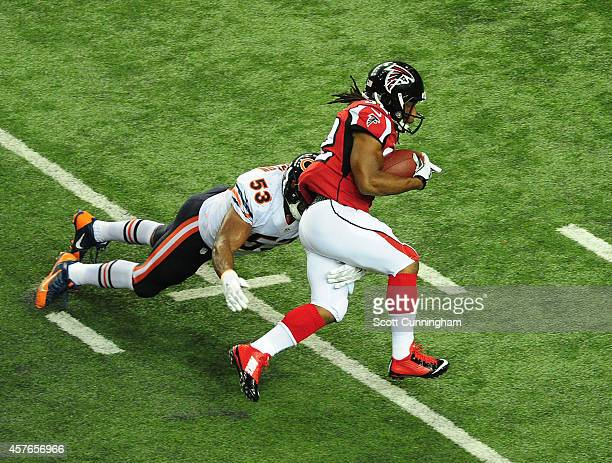 Jacquizz Rodgers of the Atlanta Falcons carries the ball against Darryl Sharpton of the Chicago Bears at the Georgia Dome on October 12 2014 in...
