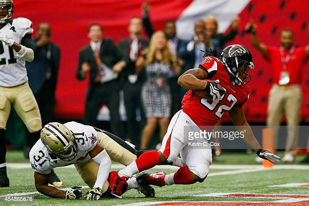 Jacquizz Rodgers of the Atlanta Falcons runs the ball for a touchdown past Jairus Byrd of the New Orleans Saints in the second half at the Georgia...