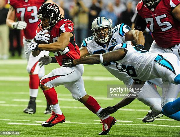 Jacquizz Rodgers of the Atlanta Falcons runs the ball in the first half against the Carolina Panthers at the Georgia Dome on December 28 2014 in...