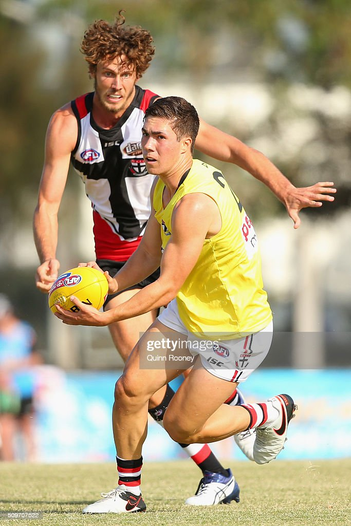 Jade Gresham of the Saints looks to handball whilst being chased by Tom Hickey during the St Kilda Saints AFL Intra-Club Match at Trevor Barker Beach Oval on February 12, 2016 in Melbourne, Australia.