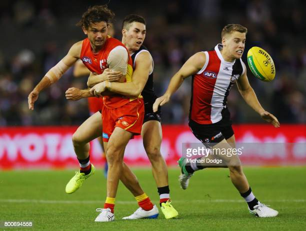 Jade Gresham of the Saints tackles Jarrod Harbrow of the Suns as Jack Lonie roves the spill of the ball during the round 14 AFL match between the St...