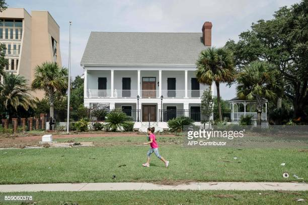 Jade Herring plays in the front yard of her grandparents' home while they survey damage to their house in the aftermath of Hurricane Nate in Biloxi...