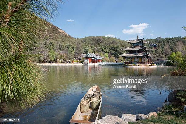 Jade Spring Park and Black Dragon Pool with boat carrying wicker baskets, and Moon Embracing Pavilion, Lijiang, Yunnan, China, Asia