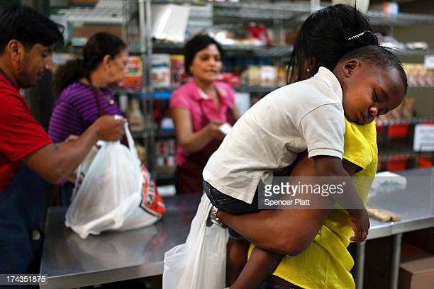 Jaden Painegua rests on his mother's shoulder at the West Side Campaign Against Hunger food bank on July 24 2013 in New York City The food bank...