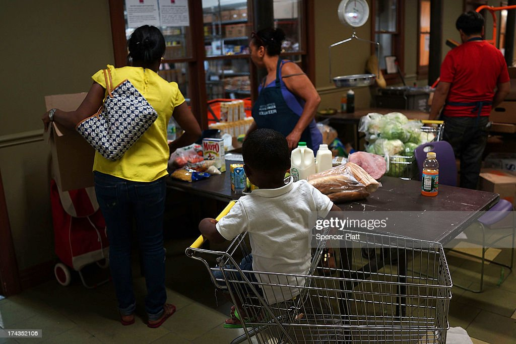 Jaden Painegua (2) watches as his mother at the West Side Campaign Against Hunger food pantry as his mother shops for food on July 24, 2013 in New York City. The food pantry assists thousands of qualifying New York residents in providing a monthly allotment of food. In an anticipated speech today in Illinois, President Obama tried to re-focus the nations attention back onto the economy and the growing inequality between the rich and the rest of America. As of May 2013 the unemployment rate in America was stuck at 7.6% with many more Americans having given up on looking for work.