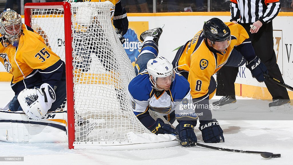 Jaden Schwartz #9 of the St. Louis Blues battles for the puck against Kevin Klein #8 as goalie <a gi-track='captionPersonalityLinkClicked' href=/galleries/search?phrase=Pekka+Rinne&family=editorial&specificpeople=2118342 ng-click='$event.stopPropagation()'>Pekka Rinne</a> #35 of the Nashville Predators minds the net during an NHL game at the Bridgestone Arena on January 21, 2013 in Nashville, Tennessee.