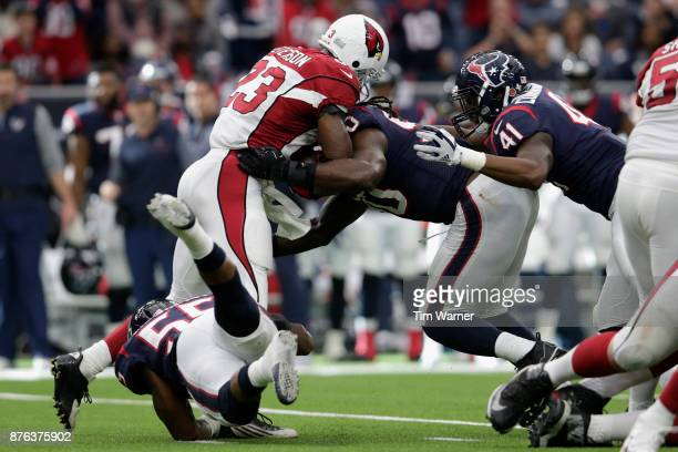 Jadeveon Clowney of the Houston Texans and Benardrick McKinney tackle Adrian Peterson of the Arizona Cardinals for a loss in the fourth quarter at...