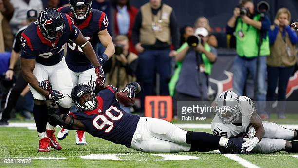 Jadeveon Clowney of the Houston Texans tips and intercepts a pass from Connor Cook of the Oakland Raiders during the first quarter of their AFC Wild...