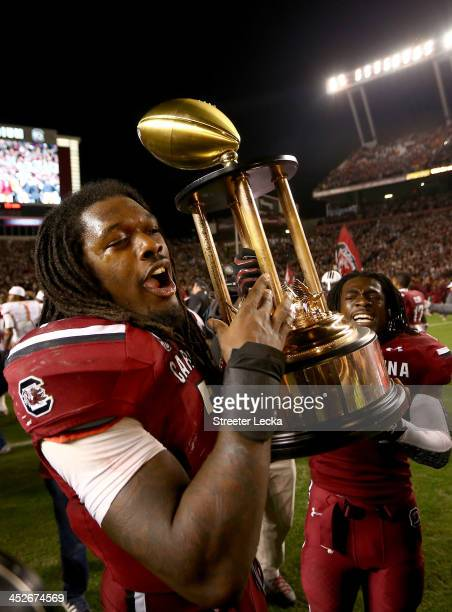 Jadeveon Clowney of the South Carolina Gamecocks and teammate Victor Hampton celebrate after defeating the Clemson Tigers 3117 after their game at...