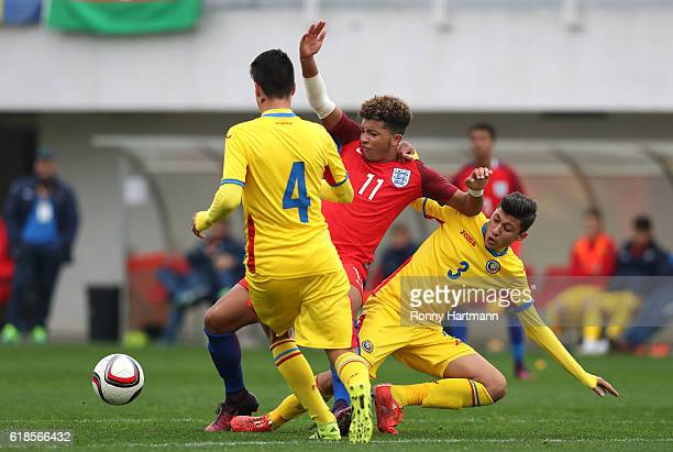 Jadon Sancho of England is attacked by Ricardo Farcas and Darius Tieranu of Romania during the UEFA Under17 EURO Qualifier between U17 England and...