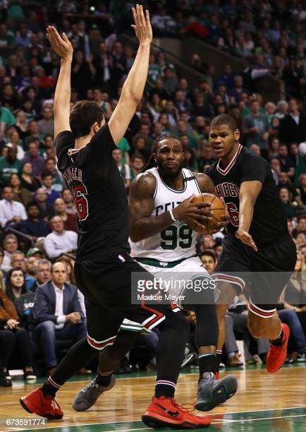 Jae Crowder of the Boston Celtics dribbles between Cristiano Felicio and Paul Zipser of the Chicago Bulls during the third quarter of Game Five of...