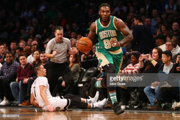 Jae Crowder of the Boston Celtics dribbles the ball as Jeremy Lin of the Brooklyn Nets fall to the court at Barclays Center on March 17 2017 in New...