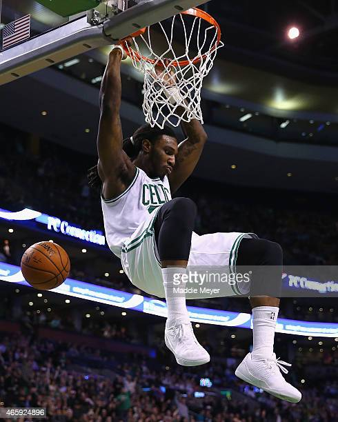 Jae Crowder of the Boston Celtics hangs from the rim after dunking against Memphis Grizzlies at TD Garden on March 11 2015 in Boston Massachusetts...