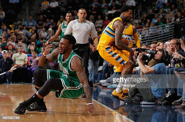 Jae Crowder of the Boston Celtics reacts after being fouled by Wilson Chandler of the Denver Nuggets ask he crashes into a cameraman chasing a loose...