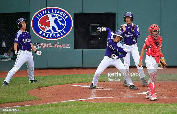Jae Yeong Hwang and Ji Ho Park look on as Dong Hwan Ahn of Team AsiaPacific celebrates scoring a run in front of catcher Shingo Tomita of Team Japan...