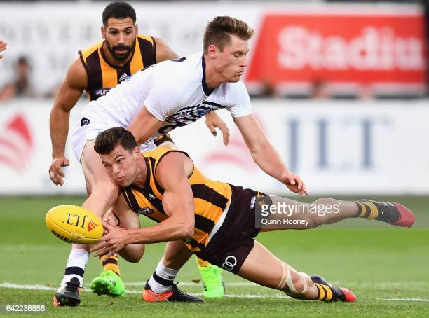 Jaeger O'Meara of the Hawks handballs whilst being tackled by Mark Blicavs of the Cats during the 2017 JLT Community Series match between the...