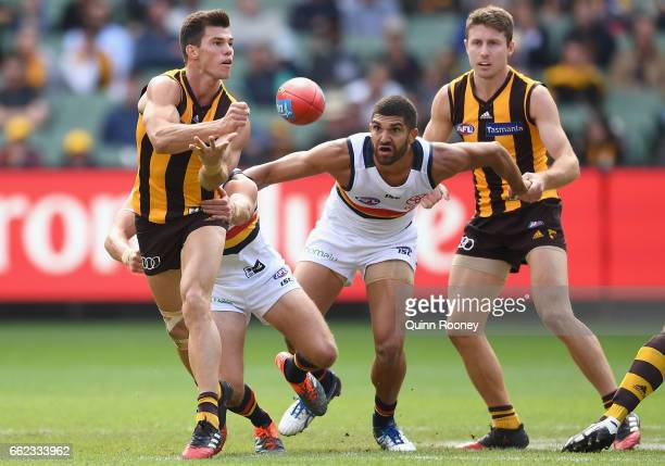 Jaeger O'Meara of the Hawks handballs whilst being tackled during the round two AFL match between the Hawthorn Hawks and the Adelaide Crows at...