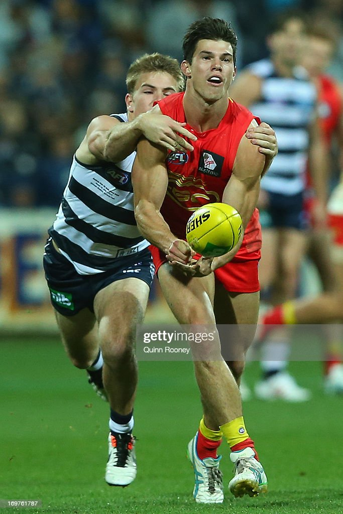 Jaeger O'Meara of the Suns handballs whilst being tackled by Jordan Schroder of the Cats during the round ten AFL match between the Geelong Cats and the Gold Coast Suns at Simonds Stadium on June 1, 2013 in Geelong, Australia.