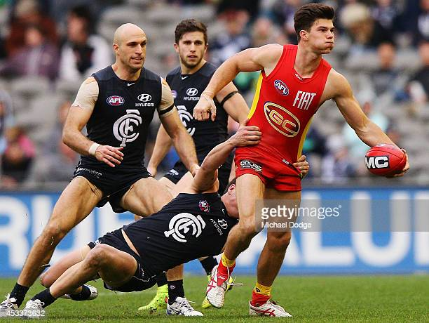 Jaeger O'Meara of the Suns is tackled by David Ellard of the Blues during the round 20 AFL match between the Carlton Blues and the GOld Coast Titans...