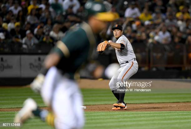 JaeGyun Hwang of the San Francisco Giants looks to throw to first base to throw out Khris Davis of the Oakland Athletics in the bottom of the fifth...