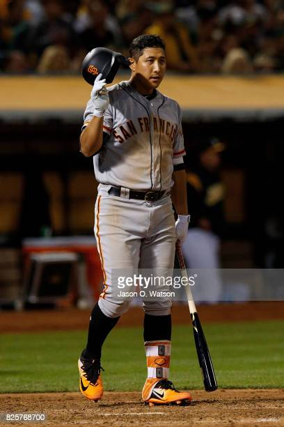 JaeGyun Hwang of the San Francisco Giants reacts after striking out against the Oakland Athletics during the sixth inning at the Oakland Coliseum on...