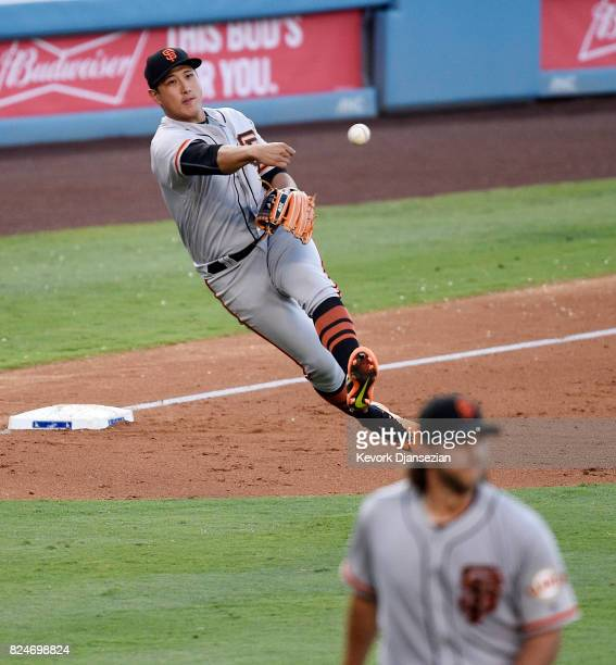 JaeGyun Hwang of the San Francisco Giants throws on the run to first base but unable to throw out Enrique Hernandez of the Los Angeles Dodgers during...