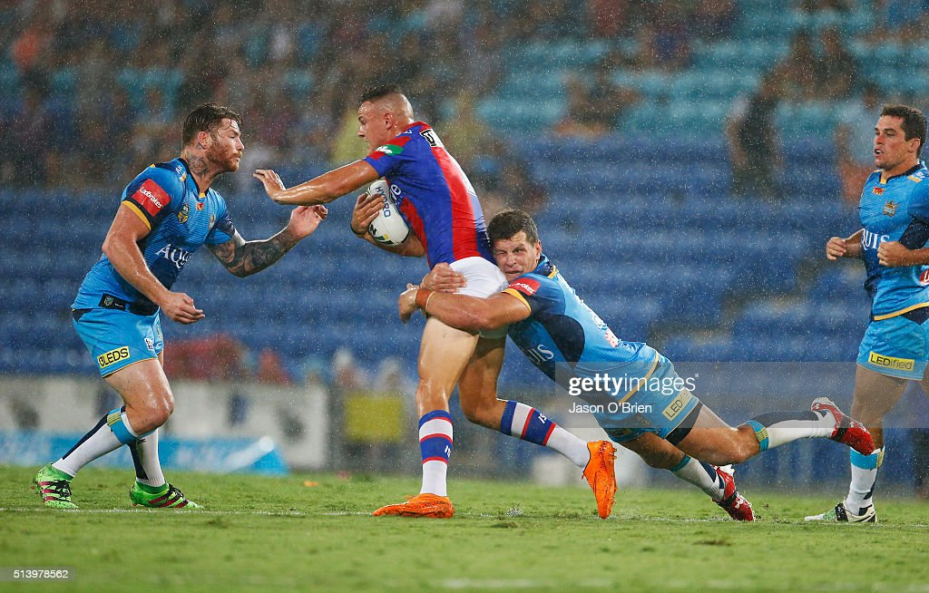 Jaeleen Feeney of the Kinights is tackled by Chris Mcqueen and Greg Bird of the Titans during the round one NRL match between the Gold Coast Titans and the Newcastle Knights at Cbus Super Stadium on March 6, 2016 in Gold Coast, Australia.