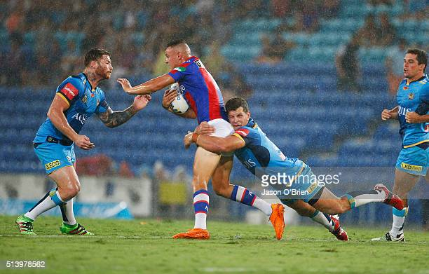 Jaeleen Feeney of the Kinights is tackled by Chris Mcqueen and Greg Bird of the Titans during the round one NRL match between the Gold Coast Titans...